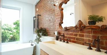 Дизайн на баня с тухлена стена като акцент