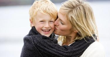 Mother kissing son at beach smiling